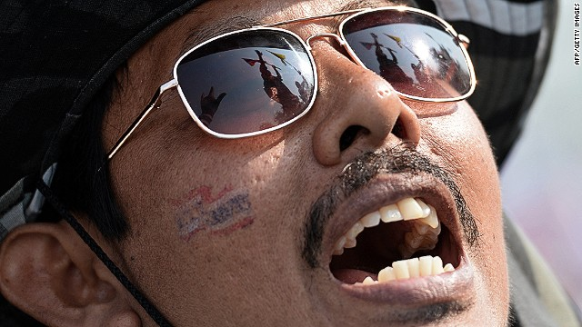 The flags of anti-government protesters are reflected in a protester's glasses in Bangkok on December 9, 2013.