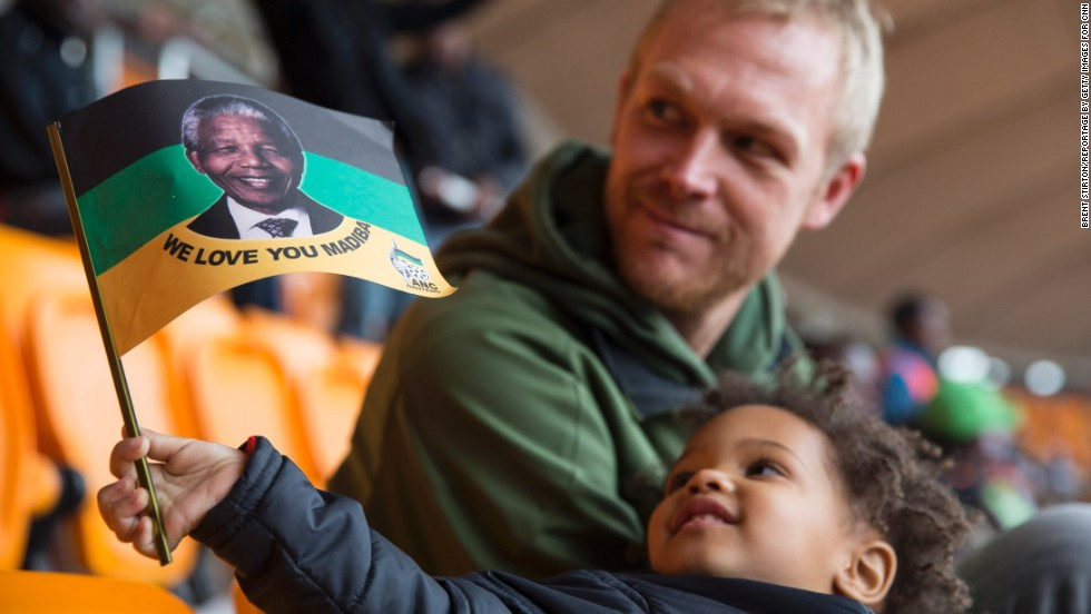 "A young boy holds up a flag honoring ""Madiba,"" Mandela's traditional clan name."