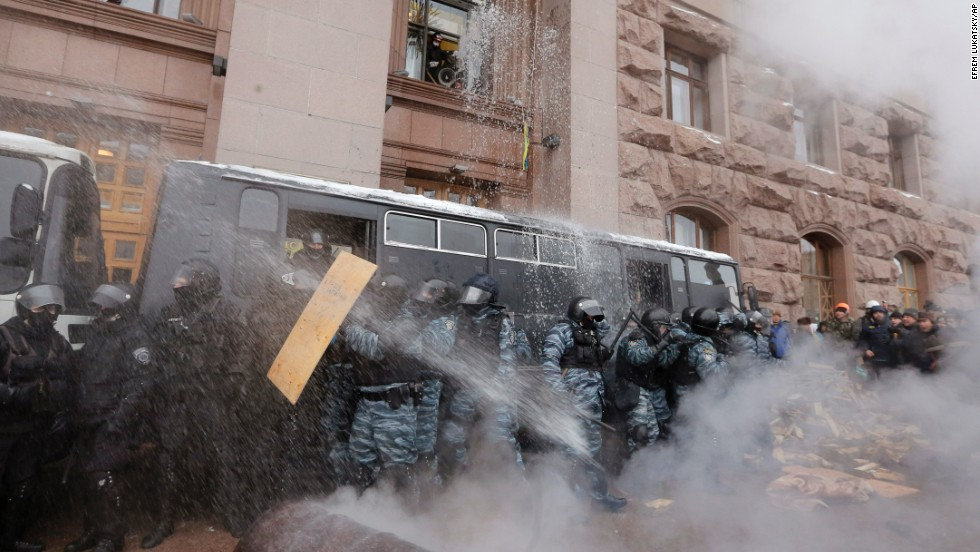 Riot police officers block the entrance of Kiev's City Hall as protesters pour water from windows and throw smoke grenades at them on December 11.