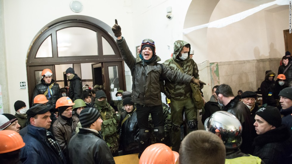 A protester calls for attention inside Kiev's City Hall after riot police were forced out from blocking the front door on December 11.