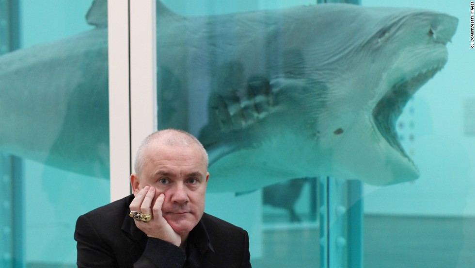 "Damien Hirst, seen here in front of one of his most famous artworks, ""The Physical Impossibility of Death in the Mind of Someone Living"" - a shark preserved in formaldehyde - was the subject of a major retrospective at London's Tate Modern gallery in 2012."