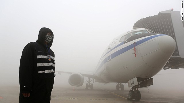 A man stands next to an airplane in heavy smog in Harbin, northeast China's Heilongjiang province, on October 21, 2013.