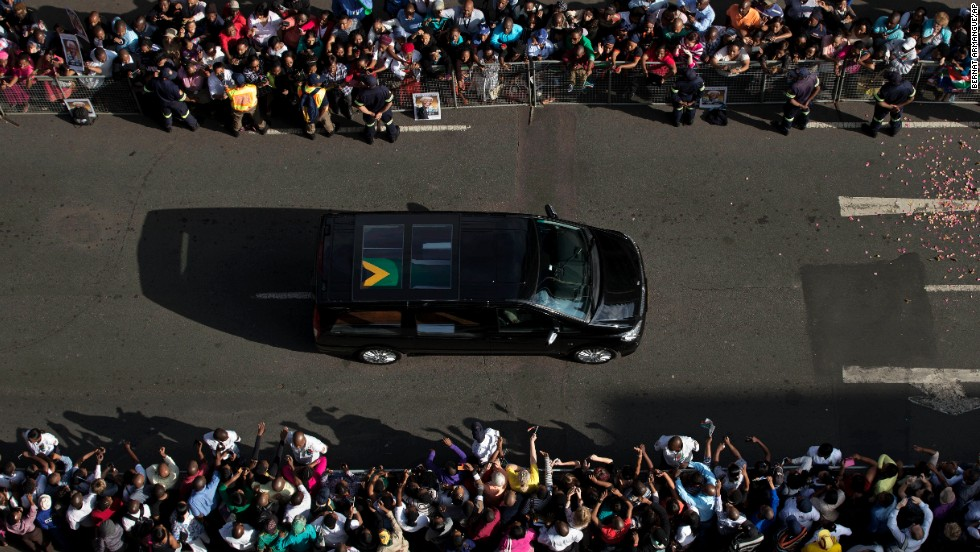Mandela's funeral procession drives toward the Union Buildings on December 12. Each morning his remains were transported from the mortuary to the government buildings.