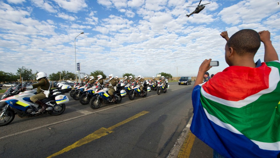 A child draped in the South African flag takes a photo of the procession as the body of Mandela arrives at the Waterkloof air base.