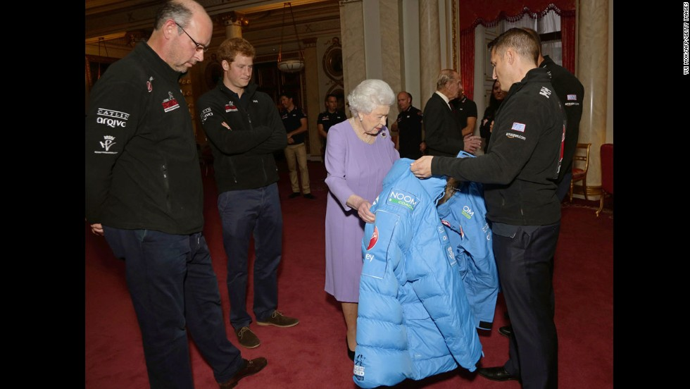 Britain's Queen Elizabeth II examines a jacket presented by a member of Team USA as her grandson looks on during a reception at Buckingham Palace in London on November 13 ahead of the Walking With the Wounded South Pole Allied Challenge.