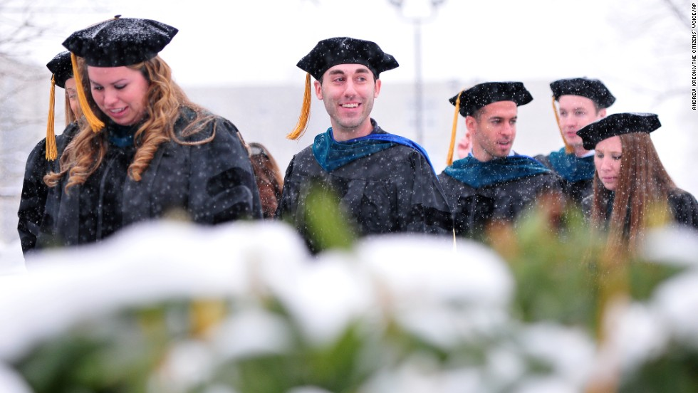 Graduates from Misericordia University make their way through the snowy campus for their commencement convocation on December 14 in Dallas, Pennsylvania.