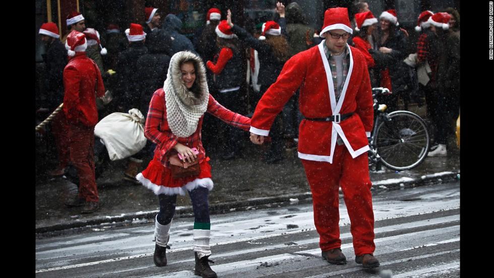 A couple dressed as Santa and Mrs. Claus cross the street in Manhattan.