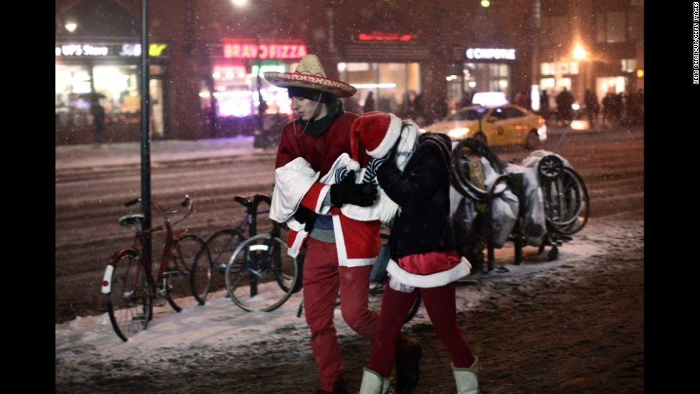 Snow falls on a couple of chilly Santas as they make their way through Manhattan.