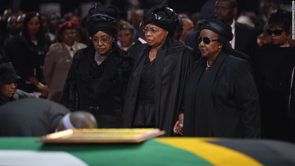 Mandela's ex-wife Winnie Madikizela Mandela, left, and his widow Graca Machel, center, stand by Mandela's casket during his funeral ceremony in Qunu on December 15.