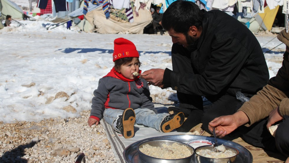 A man feeds his child in the Arsal refugee camp in Lebanon's Bekaa Valley on Sunday, December 15.