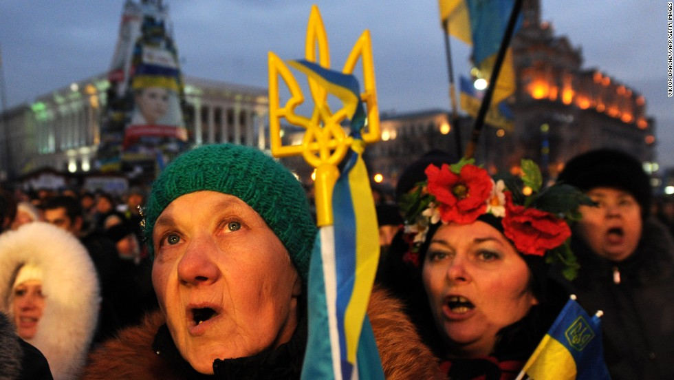People sing, shout slogans and wave Ukrainian and EU flags during a mass rally in Independence Square on December 15.