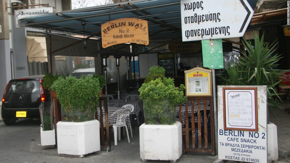 """The kebab shop Berlin No 2 sits on a barricaded street on the south side of the city. Customers order beer and souvlaki beneath a sign that reads """"Checkpoint Charlie""""."""