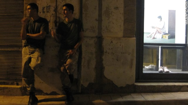 Two soldiers share a cigarette outside the The Office art gallery, Nicosia