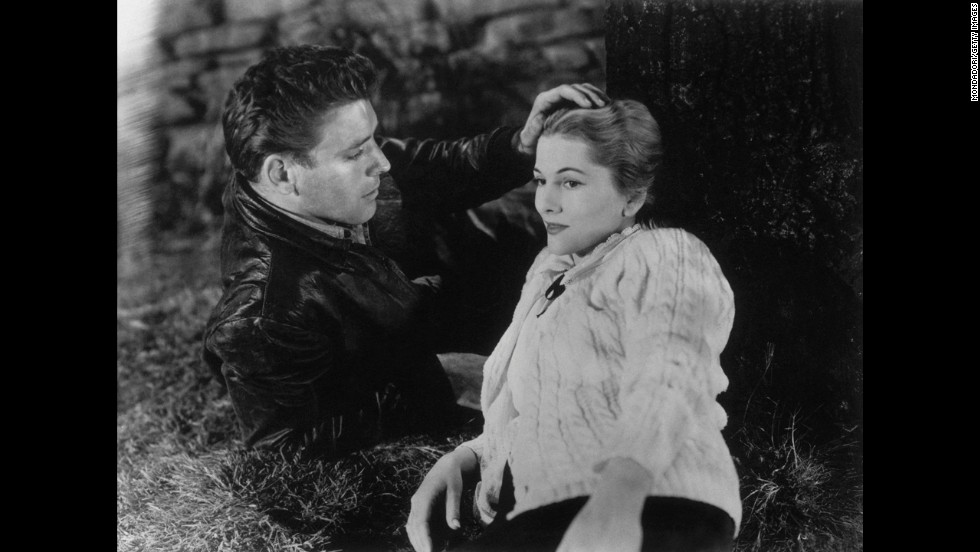 "Burt Lancaster caresses Fontaine's head in the 1948 film ""Kiss the Blood Off My Hands."""