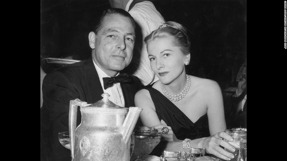 Fontaine and Collier Young sit together at a restaurant table at the Biltmore Hotel in New York City in 1956.