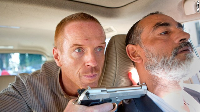 "Damian Lewis as Nicholas Brody  holds a gun on a driver in a scene from season 3 of Showtime's series ""Homeland."""