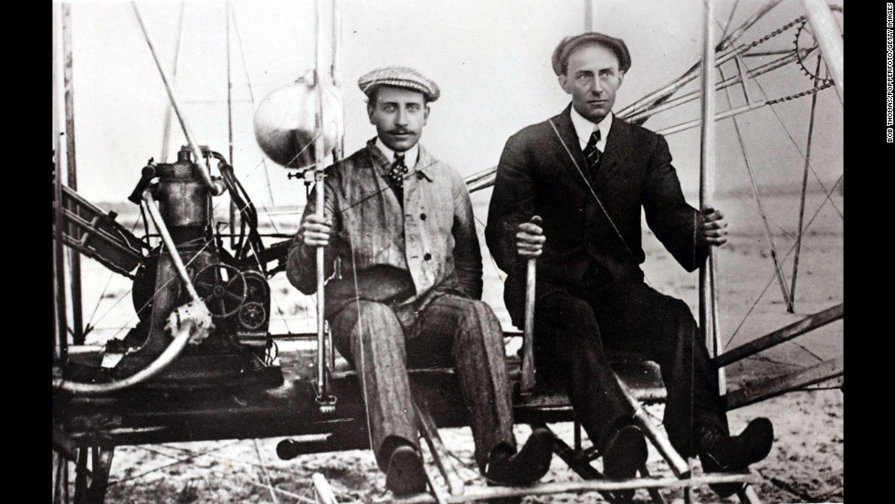 In the early 1910s, Wilbur Wright and balloonist Ernest Zens sit in the Wright Model A Flyer at Camp d'Auvours, France.