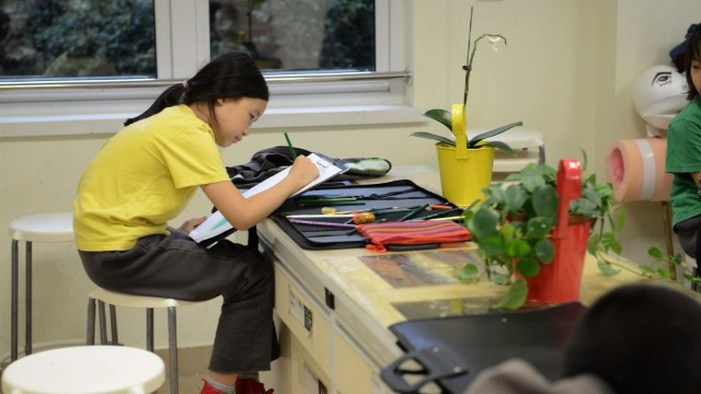 Girl does homework at Y. K. Pao School in Shanghai