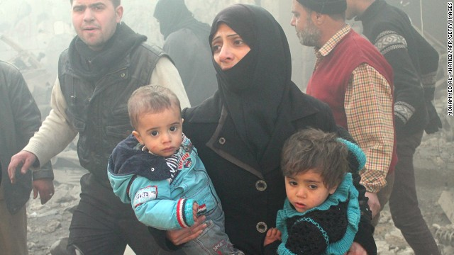 A Syrian woman carries children following airstrikes on a rebel area of the war-torn city of Aleppo on December 15, 2013.
