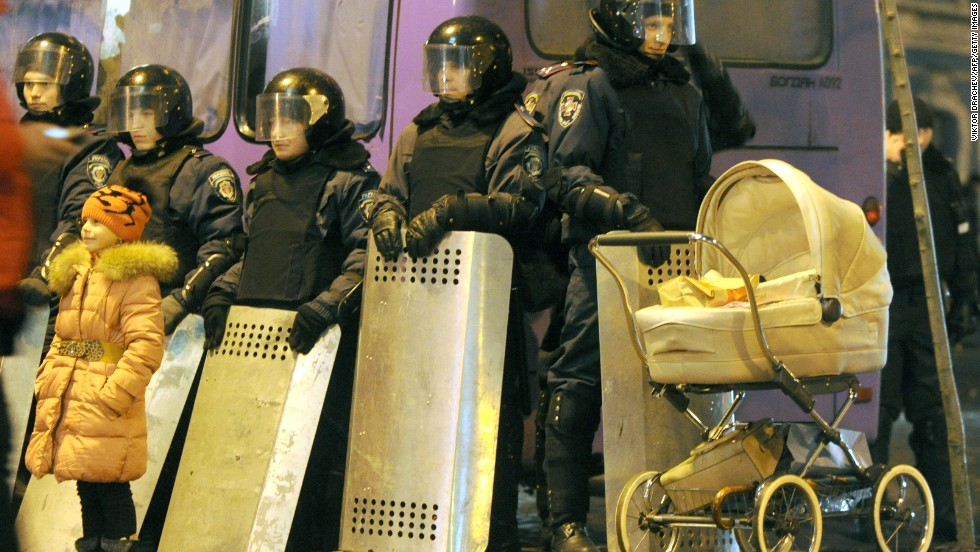 A young girl stands next to police officers guarding the presidential offices in central Kiev on December 17.