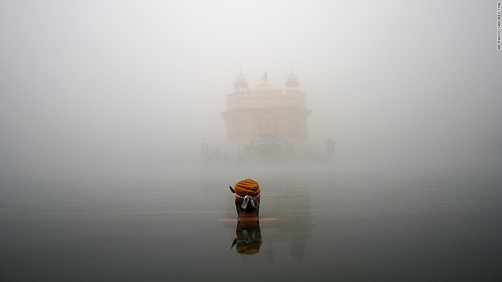 "DECEMBER 18 - AMRITSAR, INDIA: A Sikh devotee takes a holy bath in a sacred pond at the Golden Temple, the holiest Sikh shrine, amid thick fog. <a href=""http://timesofindia.indiatimes.com/india/Fog-disrupts-train-schedules-in-north-India/articleshow/27576738.cms"" target=""_blank"">The extreme weather threw rail traffic out of gear in north India for the third consecutive day, </a>according to reports."