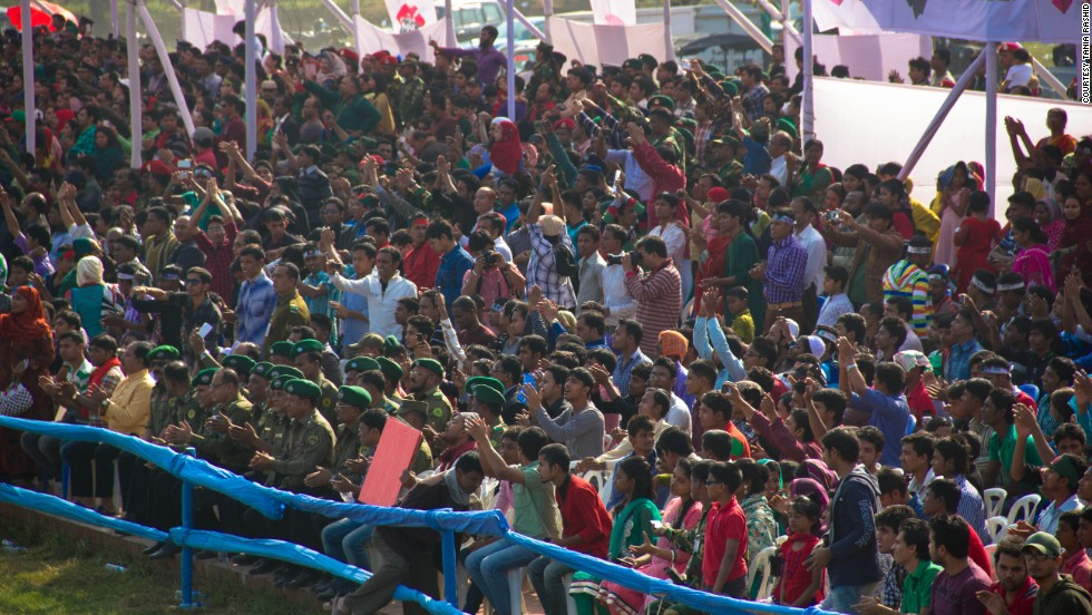 Spectators watch from the sidelines as students and army officials form a giant flag with placards at the National Parade Ground in Dhaka, Bangladesh.