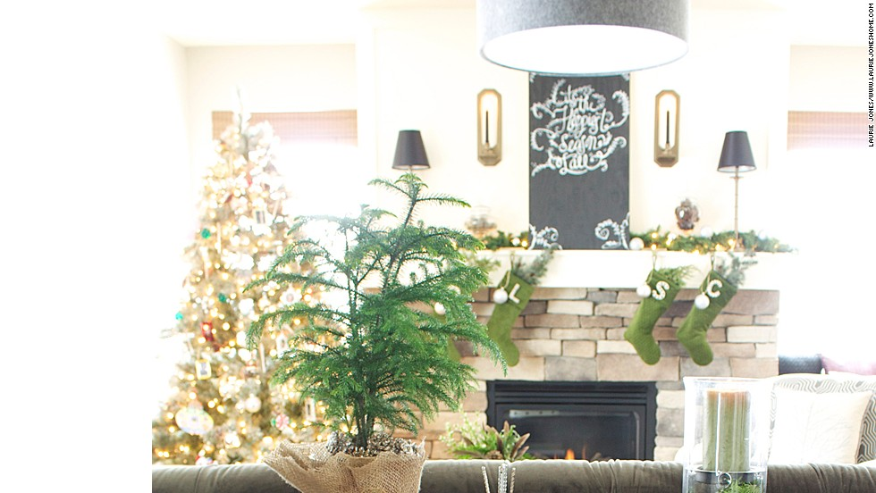 Laurie Jones uses live trees, cut greens and even moss-colored stockings to create a woodland-themed look for the holiday.