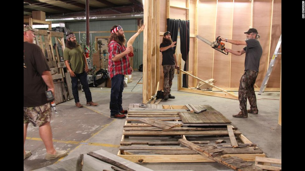 "The Duck Commander crew works on transforming their warehouse into a ""scarehouse"" during a Halloween episode. Holding the chainsaw is Si Robertson, who founded the company along with his brother Phil, not pictured."