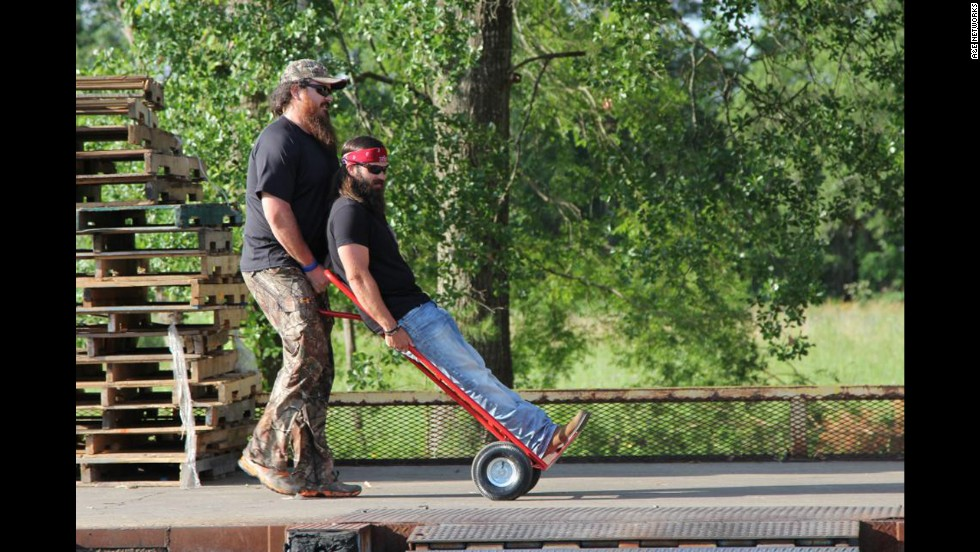 Jep Robertson, one of Willie's brothers and Phil's sons, is pushed along by Duck Commander employee Justin Martin.