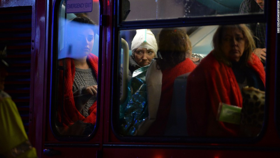 Injured people sit on a bus used for theatergoers.