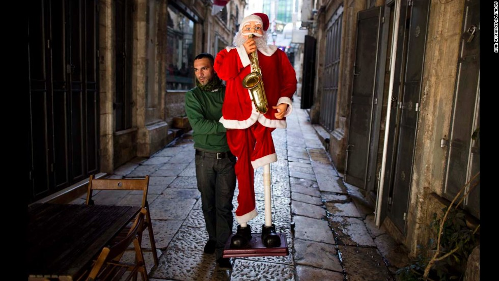 A Palestinian shop owner carries a Santa Claus figure on the street preparing for Christmas near Jaffa Gate in the Old City of Jerusalem, Israel, on December 19.