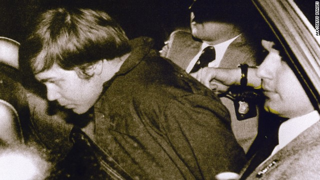 WASHINGTON, UNITED STATES: (FILES): This 30 March 1981 file photo shows John Hinckley Jr. (L) escorted by police in Washington, DC, following his arrest after shooting and seriously wounding then US president Ronald Reagan. A federal judge ruled 17 December 2003 Hinckley can make local visits with his family from St. Elizabeth's Hospital in Washington, DC, where he has been held.