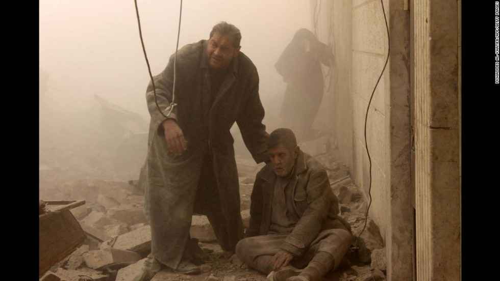 <strong>December 17: </strong>A Syrian man helps an injured man following an airstrike in Aleppo's Maadi neighborhood. Two children were among at least 13 people killed in new air strikes on a rebel-held district of Syria's main northern city of Aleppo, the Syrian Observatory for Human Rights said.
