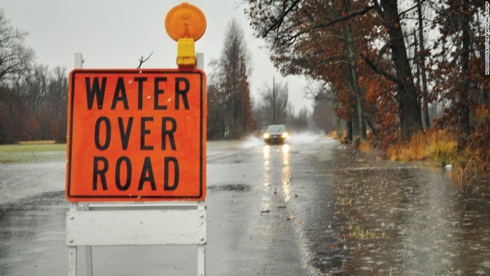 A sign warns drivers of a flooded road while a car charges through heavy rainfall on Saturday, December 21 in Paducah, Kentucky.