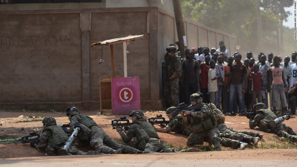 People watch as French soldiers hold their position on a street in Bangui after hearing gunshots on December 20.
