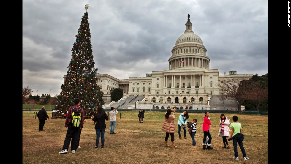 Tourists visit the U.S. Capitol Christmas tree in Washington on December 22 under cloudy skies with temperatures in the low 70s.