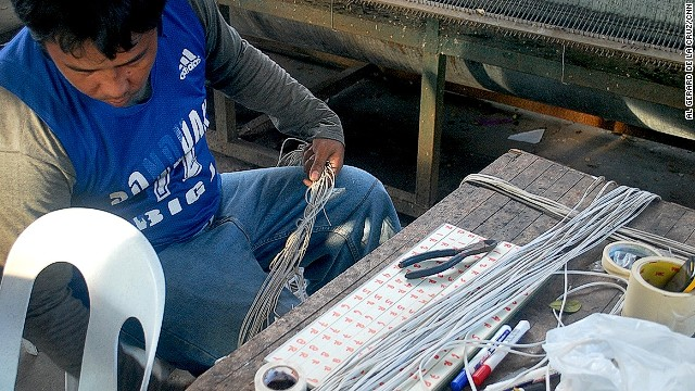 An artisan at Erning Quiwa's workshop prepares to wire the bulbs from the giant parol to the 'rotor,' the steel drum in the background.