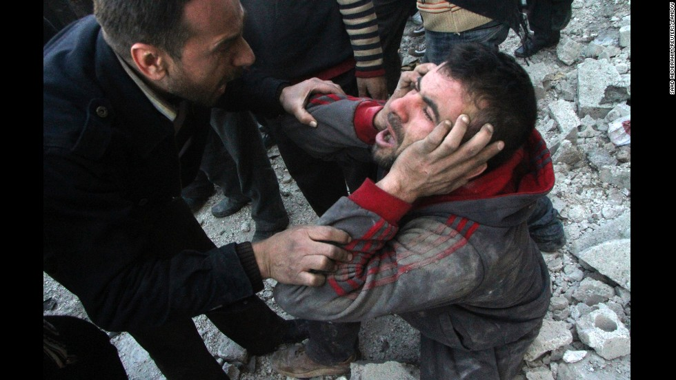 A man appears distraught after an air raid in Aleppo on Monday, December 23.
