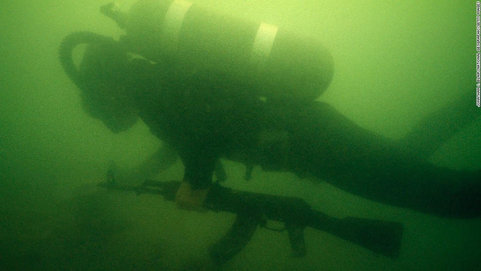 A diver retrieves an AK-47 from the bottom of the Suez Canal in Egypt in 1975.