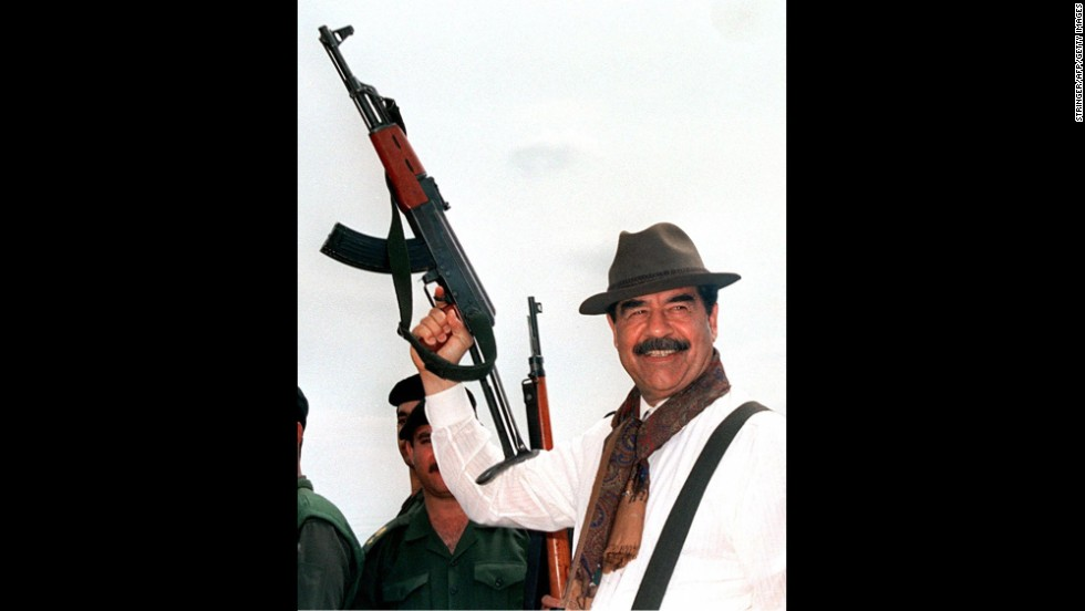 Then-Iraqi President Saddam Hussein brandishes an AK-47 during his visit to villages in northern Iraq in 1998, in this Iraqi News Agency released photograph.