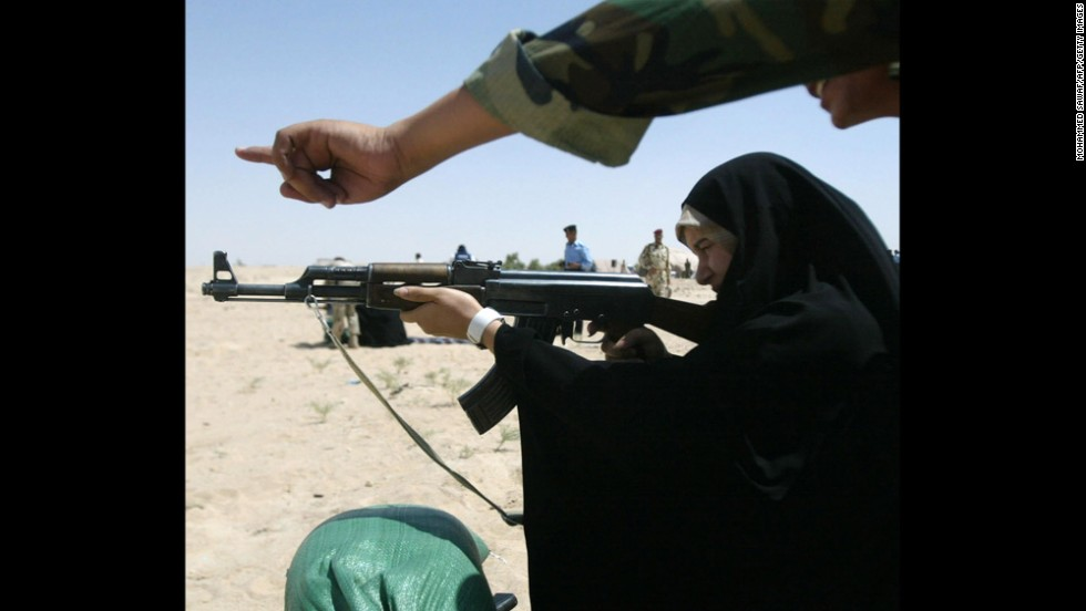 An Iraqi policewoman receives guidance firing an AK-47 during target practice in Karbala, Iraq, in 2008.