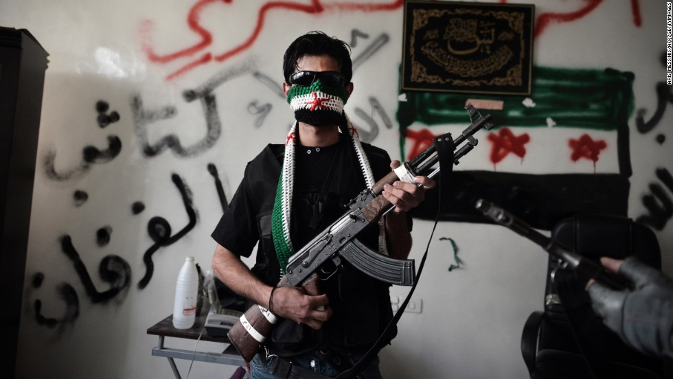 A Syrian opposition fighter poses with his AK-47 in Aleppo, Syria, in 2012.