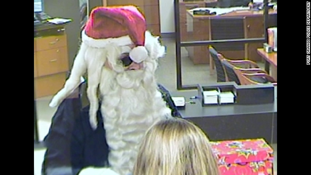 A bank robber wearing a Santa hat and beard is seen on video surveillance at a SunTrust Bank in Port Orange, Florida, on Monday, December 23.
