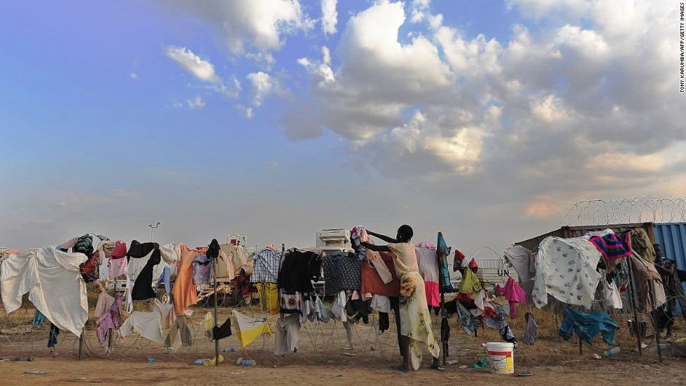 A South Sudanese girl puts her family's laundry out to dry on a barbed-wire fence at a makeshift U.N. camp in Juba on December 22.