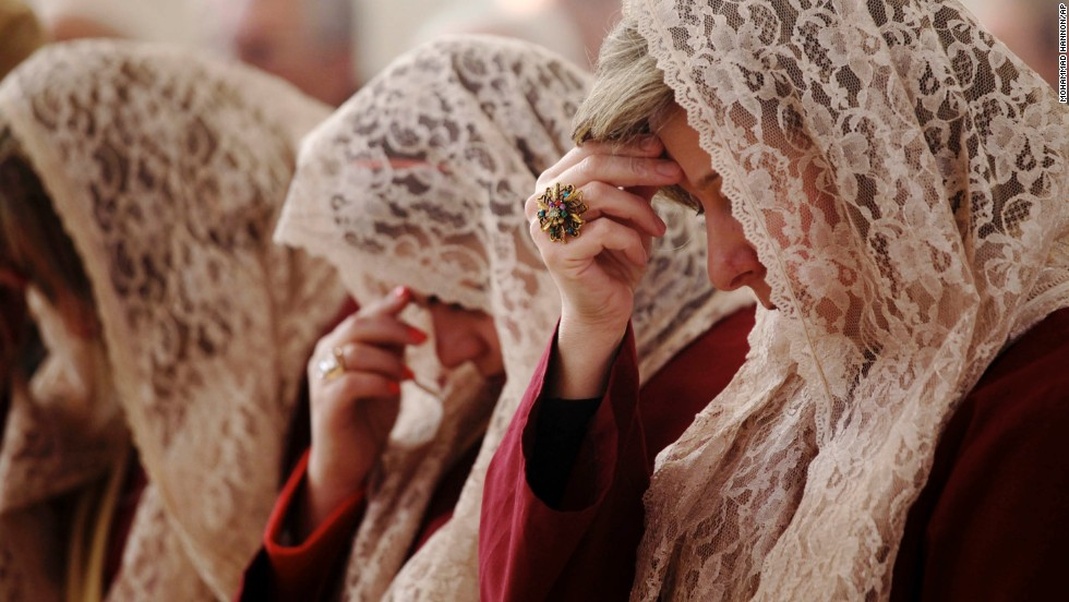 Choir members pray during a morning Mass in Amman, Jordan.