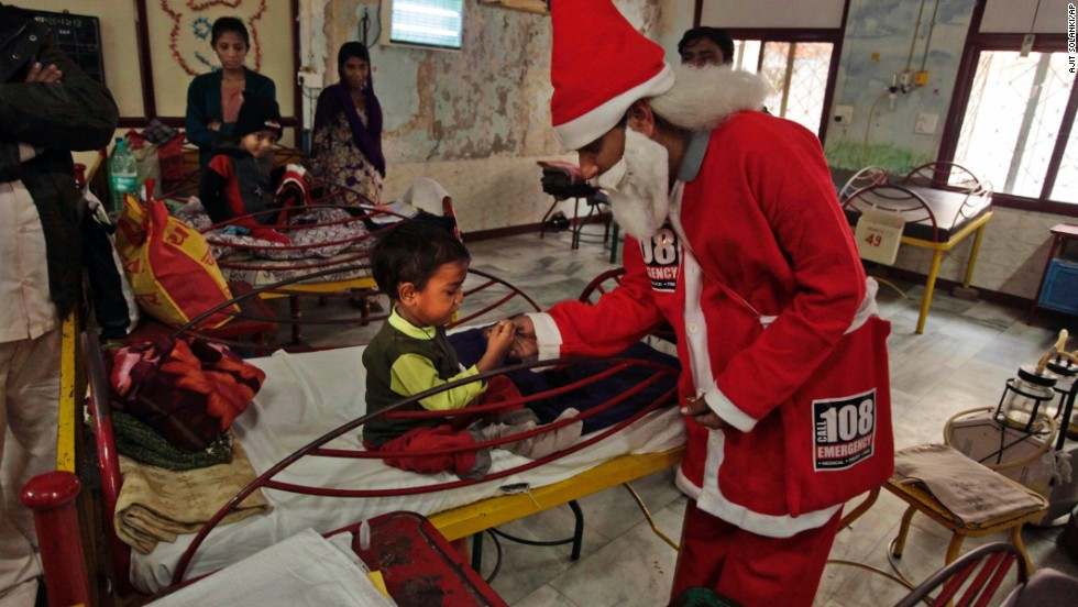 A man in a Santa outfit gives out sweets to young patients at a hospital in Ahmedabad, India.