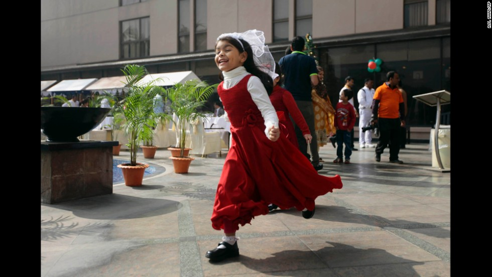 A girl runs to join a Christmas party in Dhaka, Bangladesh.