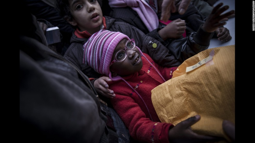 A child reaches for a gift distributed by a housing organization in Paris.