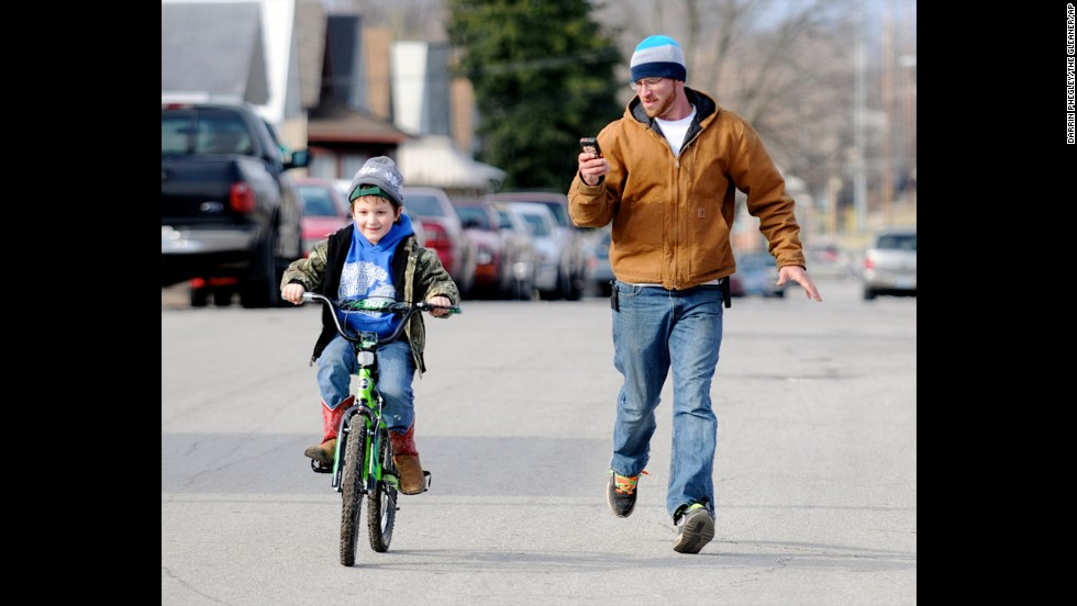 Levi Marez runs alongside his son Kaden Fletcher, 6, left, as he learns to ride the bike he got for Christmas in Henderson, Kentucky.