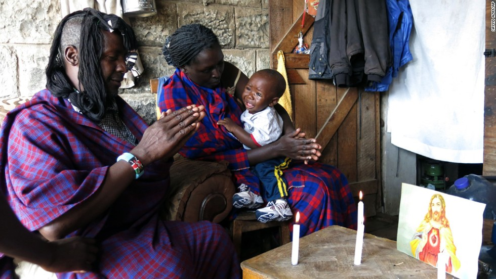 A Kenyan Christian Masai with his wife and child offer prayers in front of a small picture of Jesus at his home in the outskirts of Nairobi Kenya.